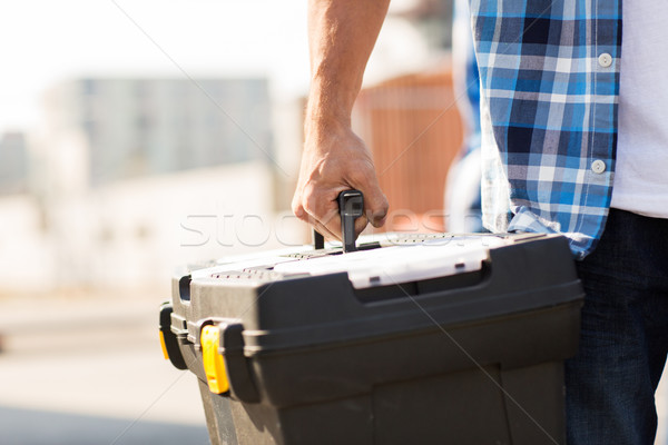 close up of builder carrying toolbox outdoors Stock photo © dolgachov