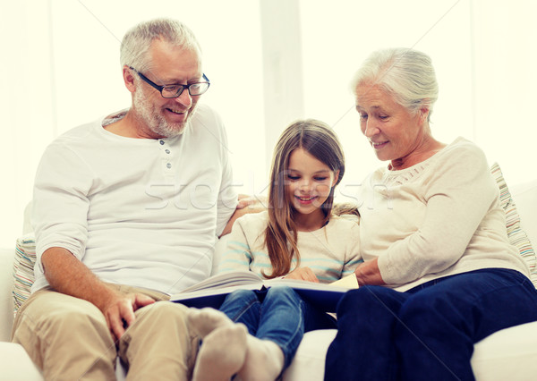 Stock photo: smiling family with book at home