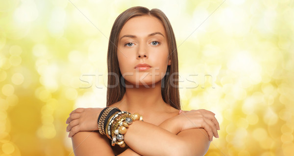 beautiful woman with bracelets over yellow lights Stock photo © dolgachov