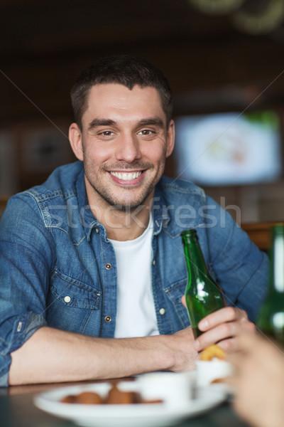 Szczęśliwy młody człowiek pitnej piwa bar publikacji Zdjęcia stock © dolgachov