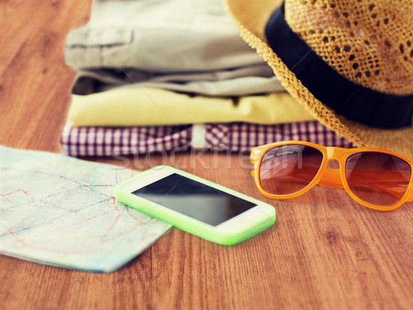 close up of summer clothes and travel map on floor Stock photo © dolgachov