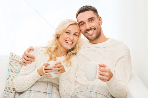 Stock photo: happy couple with cups drinking tea at home