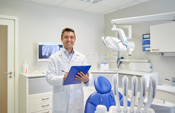 happy male dentist with clipboard at dental clinic Stock photo © dolgachov