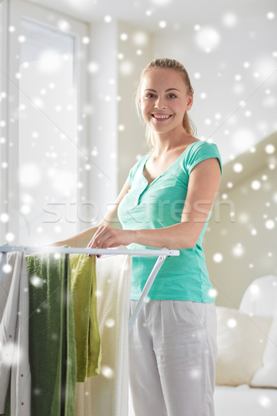 Stock photo: happy woman hanging clothes on dryer at home