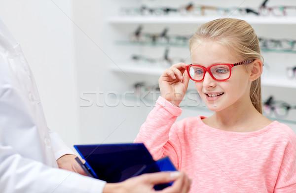 Oculista menina escolher óculos ótica armazenar Foto stock © dolgachov