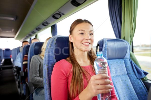 Heureux jeune femme une bouteille d'eau Voyage bus transport Photo stock © dolgachov