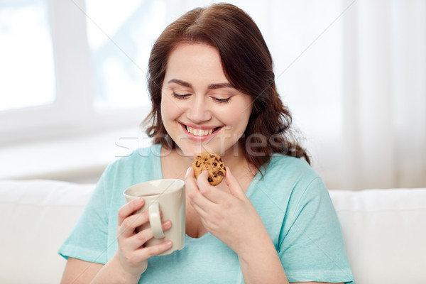happy plus size woman with cup and cookie at home Stock photo © dolgachov