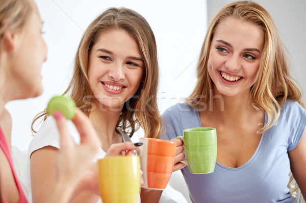 Stock photo: happy young women drinking tea with sweets at home