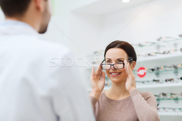 woman choosing glasses at optics store Stock photo © dolgachov