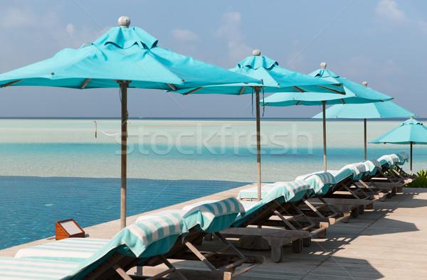 parasol and sunbeds by sea on maldives beach Stock photo © dolgachov