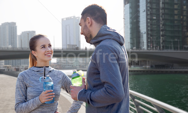 smiling couple with bottles of water in city Stock photo © dolgachov