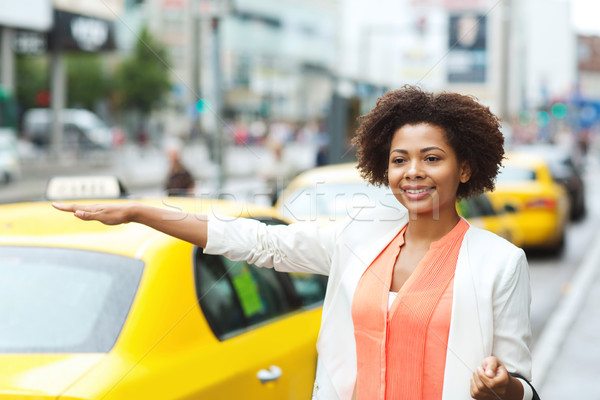 happy african woman catching taxi Stock photo © dolgachov