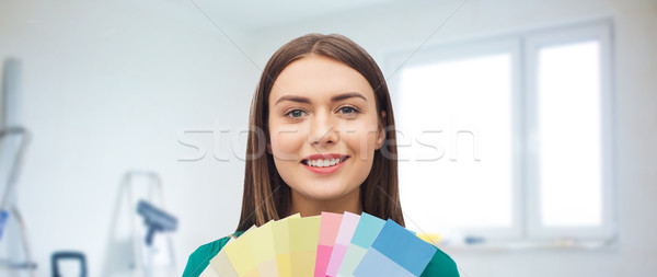 smiling young woman with color swatches Stock photo © dolgachov