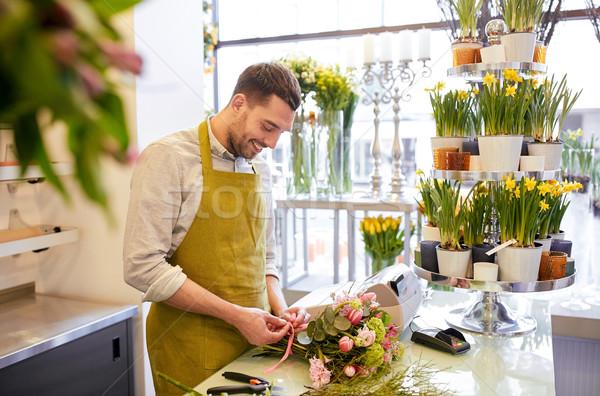 smiling florist man making bunch at flower shop Stock photo © dolgachov
