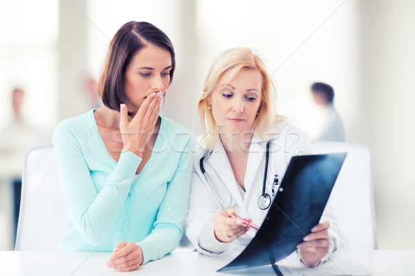 doctor with patient looking at x-ray Stock photo © dolgachov