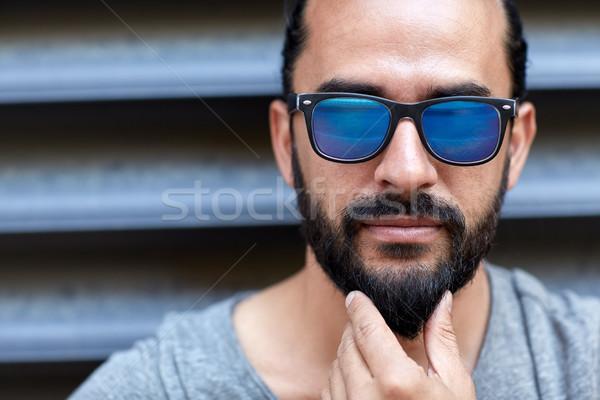 man in sunglasses touching beard on city street Stock photo © dolgachov