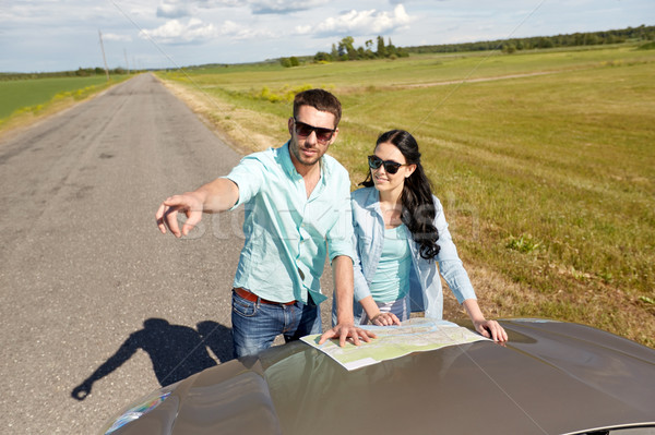 happy man and woman with road map on car hood Stock photo © dolgachov