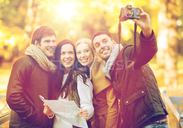 Stock photo: group of friends with photo camera in autumn park