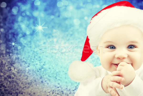 happy baby in santa hat over blue holidays lights Stock photo © dolgachov