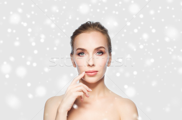beautiful young woman showing her lips over snow Stock photo © dolgachov