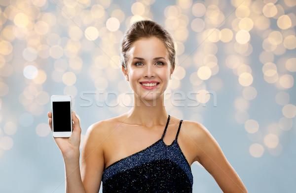 улыбающаяся женщина вечернее платье смартфон технологий реклама Сток-фото © dolgachov