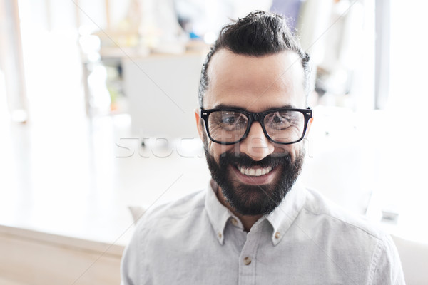 Stock photo: smiling man with eyeglasses and beard at office