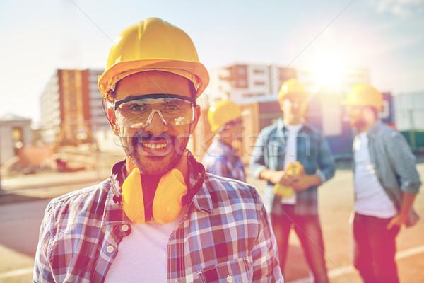 Glimlachend bouwer veiligheidshelm hoofdtelefoon business gebouw Stockfoto © dolgachov