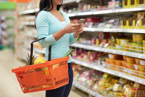 Kobieta smartphone zakupu żywności supermarket Zdjęcia stock © dolgachov
