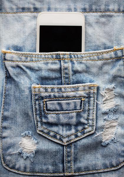 smartphone in pocket of denim overalls Stock photo © dolgachov