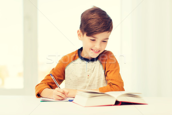 Sorridente estudante menino escrita caderno casa Foto stock © dolgachov