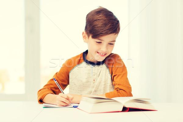 Glimlachend student jongen schrijven notebook home Stockfoto © dolgachov