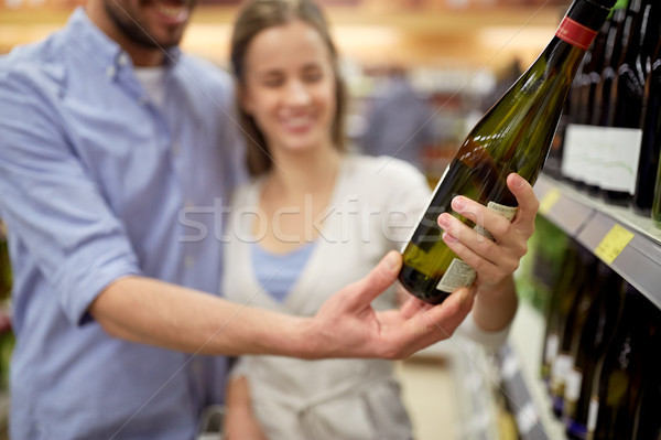 happy couple with bottle of wine at liquor store Stock photo © dolgachov