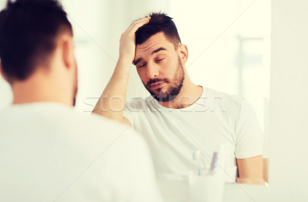 sleepy young man in front of mirror at bathroom Stock photo © dolgachov