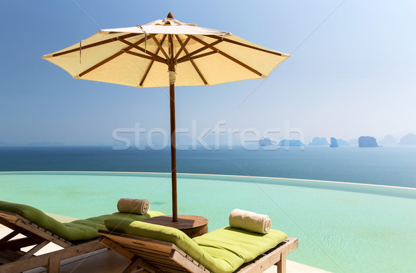 infinity pool with parasol and sun beds at ocean Stock photo © dolgachov