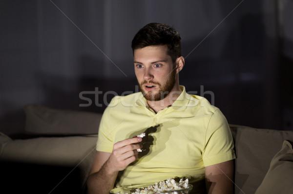 man watching tv and eating popcorn at night Stock photo © dolgachov