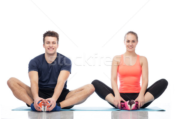 happy sportive man and woman sitting on mats Stock photo © dolgachov