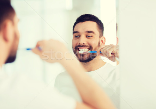 man with toothbrush cleaning teeth at bathroom Stock photo © dolgachov