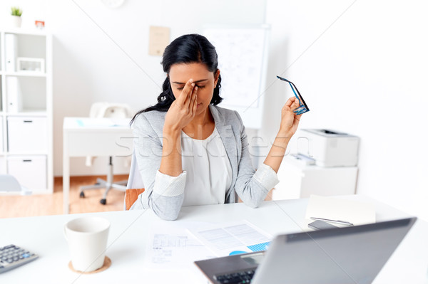 businesswoman rubbing tired eyes at office Stock photo © dolgachov