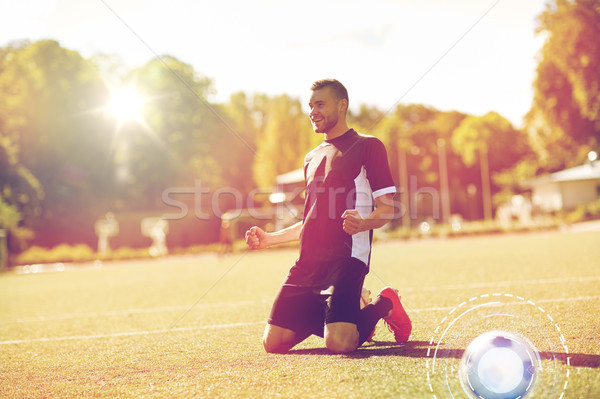 happy soccer player with ball on football field Stock photo © dolgachov
