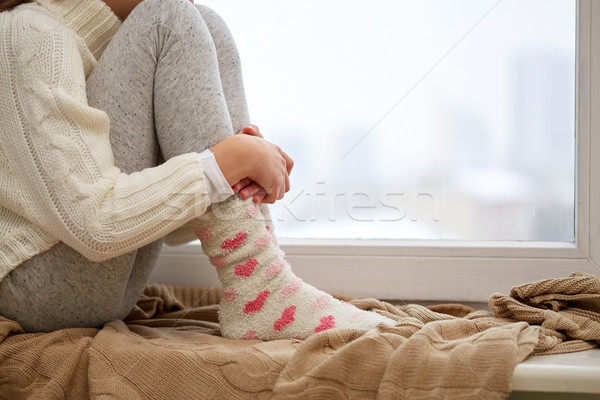 girl sitting on sill at home window in winter Stock photo © dolgachov