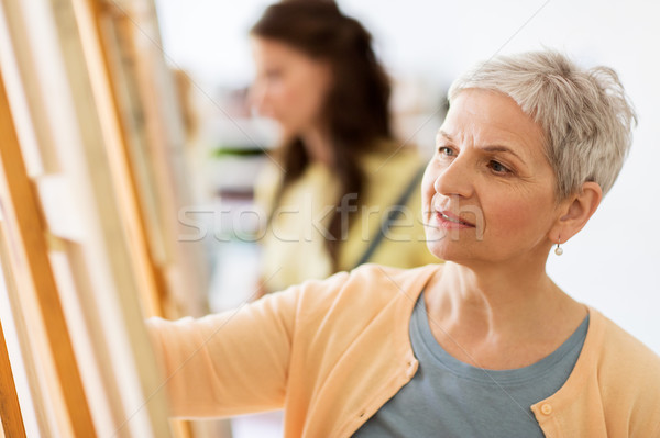 woman artist with easel drawing at art school Stock photo © dolgachov