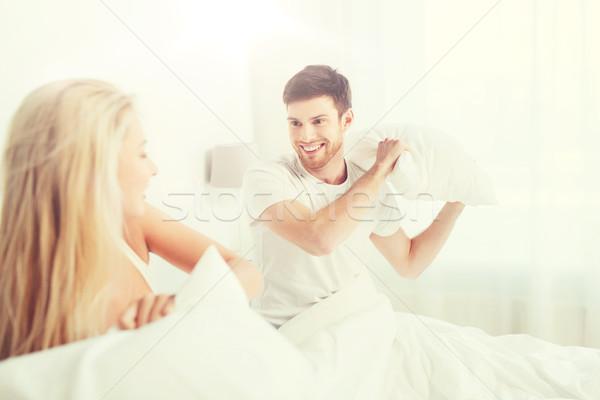 Feliz casal luta de almofadas cama casa pessoas Foto stock © dolgachov