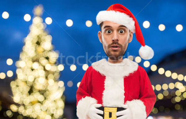 man in santa claus costume over christmas lights Stock photo © dolgachov
