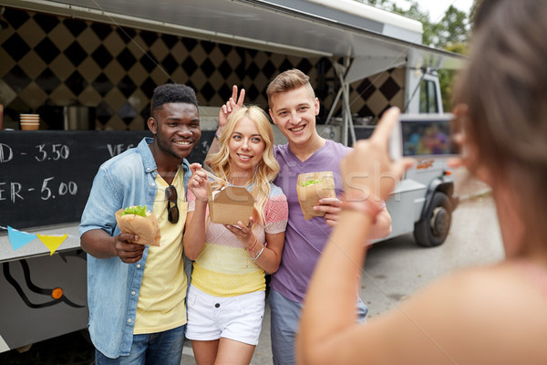 woman photographing friends eating at food truck Stock photo © dolgachov