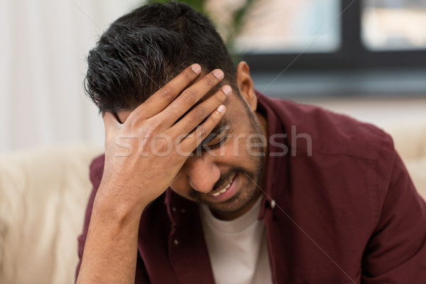 close up of man suffering from head ache at home Stock photo © dolgachov