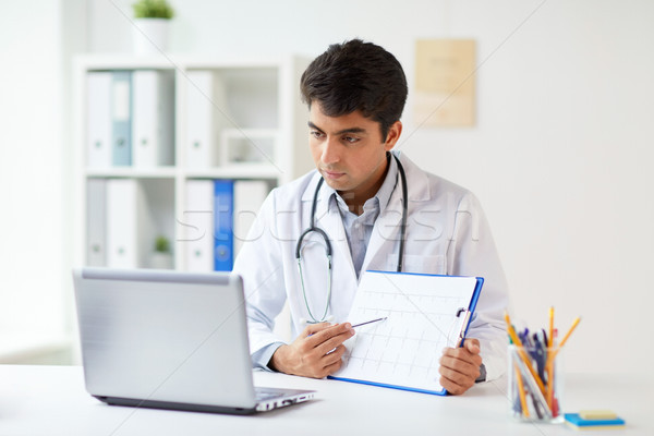 doctor with laptop and cardiogram at clinic Stock photo © dolgachov