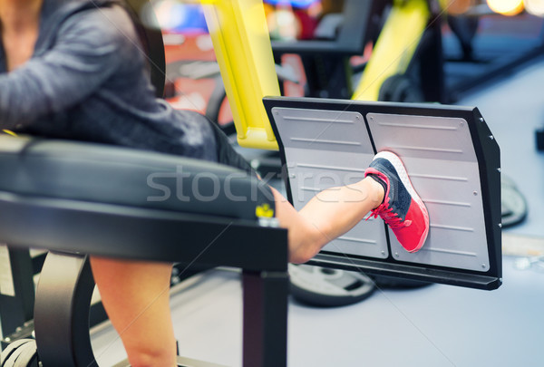 woman flexing muscles on leg press machine in gym Stock photo © dolgachov