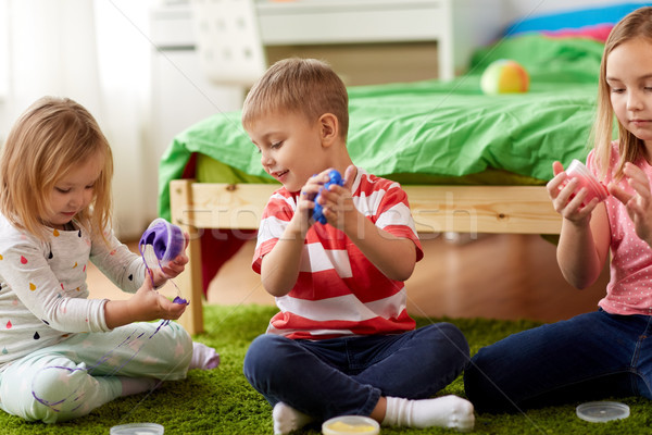 little kids with modelling clay or slimes at home Stock photo © dolgachov