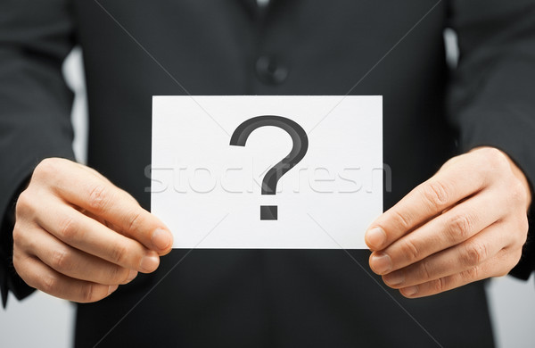 man in suit holding card with question mark Stock photo © dolgachov