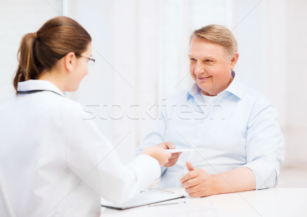 female doctor with old man giving prescription Stock photo © dolgachov